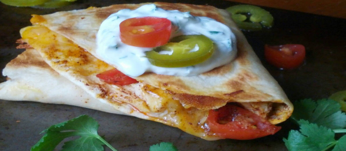 Super quick and easy chicken quesadillas are dressed up with an equally quick and easy cilantro-lime sour cream sauce.